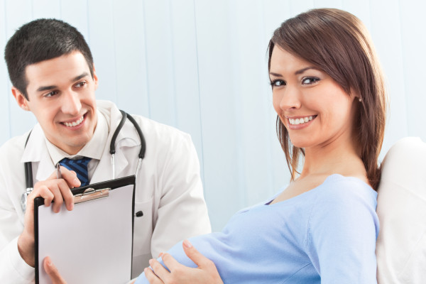Doctor and pregnant female patient on bed at clinic