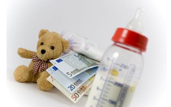 Ein Stapel Babywindeln, Schoppen,Teddybär und Geldscheine vor weißem Hintergrund